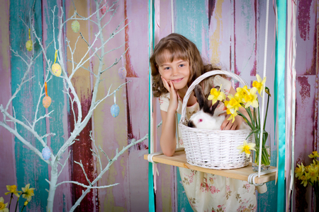 The girl and easter rabbit in a basket on a swing