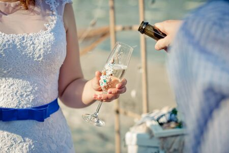 Glass with champagne is  in the brides hands. The groom is pouring champagne into the brides glass.  Sea style wedding. 版權商用圖片