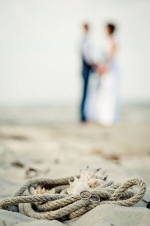 Wedding rings, sea rope, cockleshells are on  sand, silhouettes of the groom and bride in the distance.  A wedding decor in sea style.