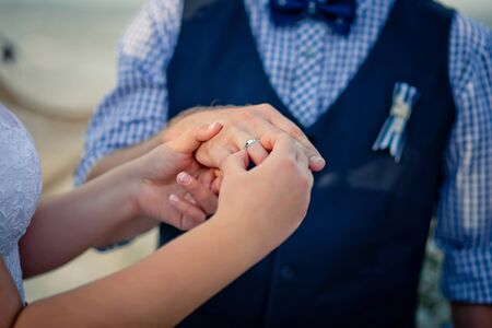 The bride puts on a wedding ring the grooms finger. Sea style wedding Zdjęcie Seryjne