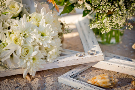 Wedding rings, bridal bouquet, cockleshells, a framework for a photo. A wedding decor in sea style.