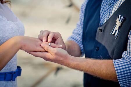 The groom puts on a wedding ring the brides finger. Sea style wedding Zdjęcie Seryjne