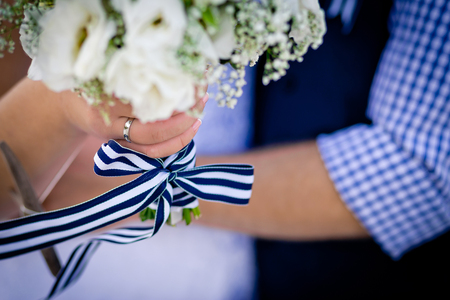 Loving couple. A wedding ring is on the brides hand, a sea style ribbon  on a wedding bouquet. Sea style wedding.