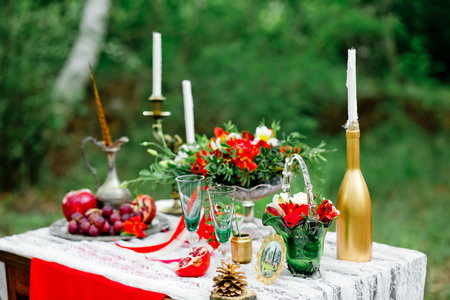 Wedding decor with fruit, flowers, candles  on a table in style of a boho-chic. Decoration of a wedding photoshoot.  Details of a wedding decor. Zdjęcie Seryjne