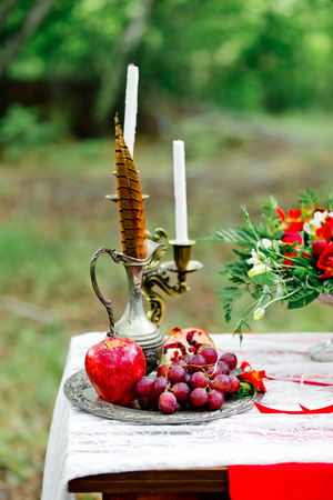 Wedding decor with fruit, flowers, candles and a pheasant feather on a table in style of a boho-chic. Decoration of a wedding photoshoot.  Details of a wedding decor. Zdjęcie Seryjne