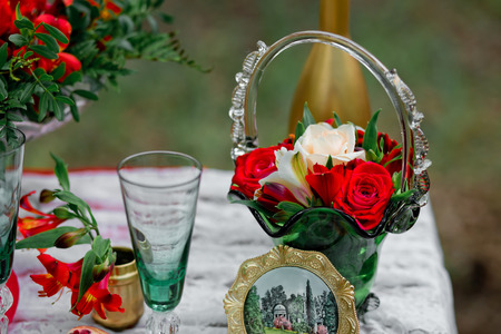 Wedding decor with green glasses and the vase with flowers of a rose and  alstroemeria on a table in style of a boho-chic. Decoration of a wedding photoshoot.  Details of a wedding decor.