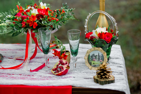 Wedding decor with green glasses, pomegranate, flowers of a rose and  alstroemeria on a table in style of a boho-chic. Decoration of a wedding photoshoot.  Details of a wedding decor.