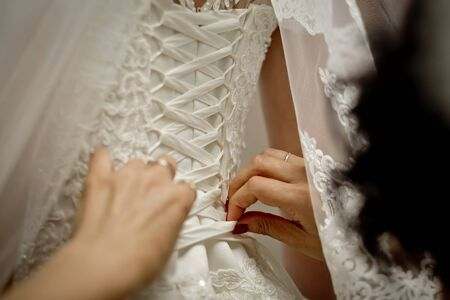 Lacing of a wedding dress of the bride. Morning gatherings of bride 版權商用圖片