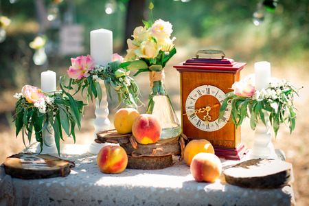 Wedding decor for photographing with the bracket clock, flowers, candles and peaches. Decoration of a wedding photoshoot.  Details of a wedding decor.