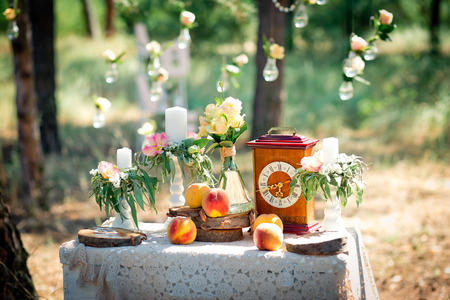Wedding decor for photographing with the bracket clock, flowers, candles and peaches on a ancient suitcase. Roses in bulbs on a background . Decoration of a wedding photoshoot.  Details of a wedding decor. Zdjęcie Seryjne