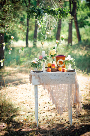 Wedding decor for photographing with the bracket clock, flowers, candles and peaches on a ancient suitcase. Roses in bulbs on a background . Decoration of a wedding photoshoot.  Details of a wedding decor. 版權商用圖片