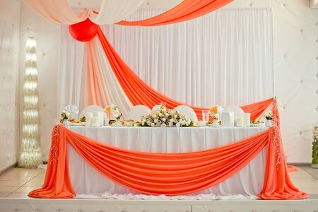 Decorative elements of a wedding table at the wedding banquet. Wedding in orange color. Table for newly married.
