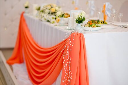 Decorative elements of a wedding table at the wedding banquet. Wedding in orange color
