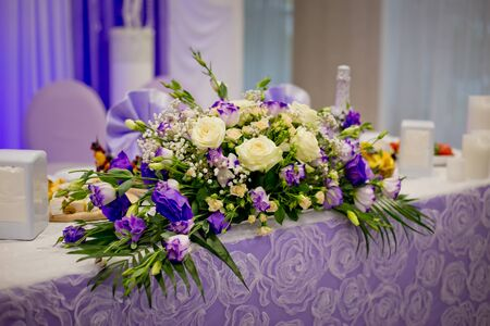 Decorative elements of a wedding table at the wedding banquet - flower composition. Wedding in lilac and violet color