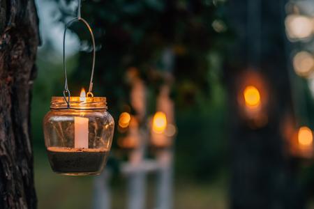 La lámpara hecha de un tarro con una vela está colgando en un árbol por la noche. Decoración de la noche de la boda. Ceremonia nocturna Foto de archivo