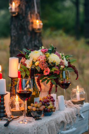 Wedding decor with  glasses, flowers, vases, candles and fruit on a ancient suitcase. Decoration of a wedding photoshoot.  Details of a wedding decor.