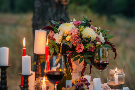 Wedding bouquet  with  glasses, vine,  candles and fruit outdoor. Decoration of a wedding photoshoot.  Details of a wedding decor. Zdjęcie Seryjne
