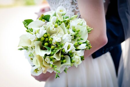 A bridal bouquet with callas, eustoma, berries in the brides hands. Floristic composition.