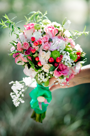A bridal bouquet with roses, eustoma, berries in the brides hand. Floristic composition.