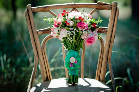 A bridal bouquet with roses, eustoma, berries A bridal bouquet on an ancient chair. Floristic composition. Zdjęcie Seryjne