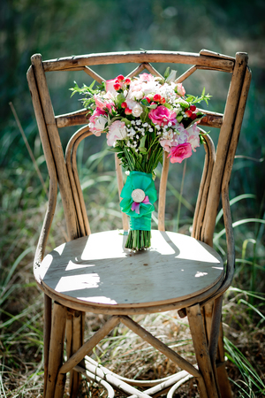 A bridal bouquet with roses, eustoma, berries A bridal bouquet on an ancient chair. Floristic composition. 版權商用圖片