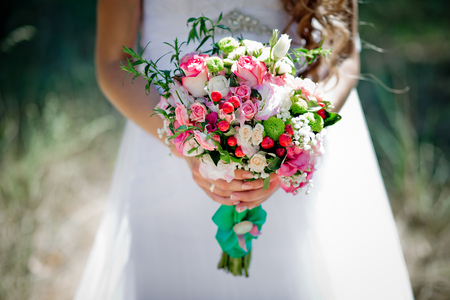 A bridal bouquet with roses, eustoma, berries in the brides hands. Floristic composition.
