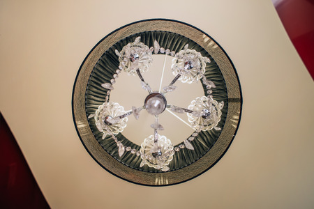 Crystal chandelier with a black lamp shade under a stretch ceiling - top view, bottom view. An interior of Artdeco.  版權商用圖片