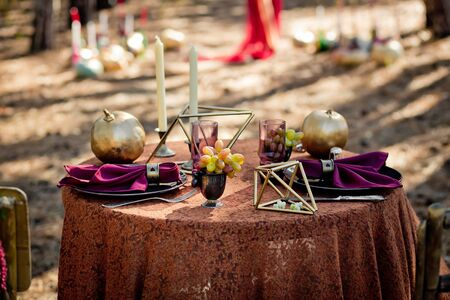 The table with an autumn decor laid for two in the wood. Appointment, Halloween, autumn wedding.