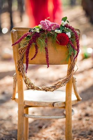 Wreath from a rod with autumn flowers hanging on a ancient chair in the wood. Paints of fall in the coniferous wood.