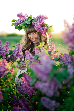 The young pregnant woman with a wreath on her head is looking through a lilac bush