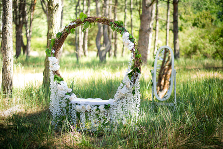 Wedding decor. Scenery for a wedding photoshoot in the forest. The big ring wattled of a rod and white florets Zdjęcie Seryjne