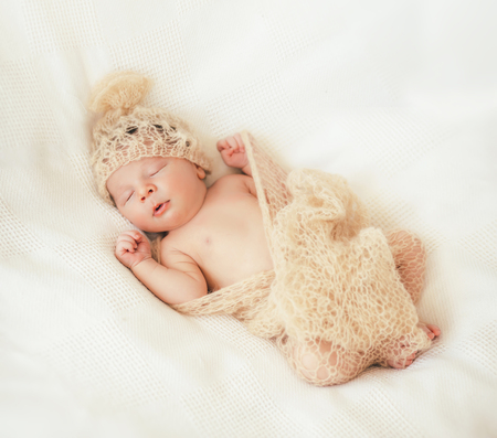 Cute little baby is  sleeping in a gentle knitted blanket of cream color 版權商用圖片