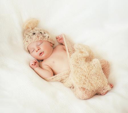 Cute little baby is  sleeping in a gentle knitted blanket of cream color Zdjęcie Seryjne