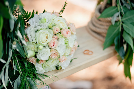 Wedding decor. A bridal bouquet on a decorative swing.Outdoor.