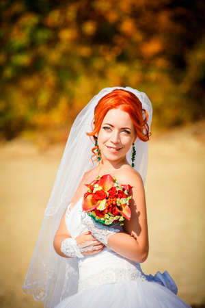 bouqet: Portrait of a beautiful redheaded bride with wedding bouqet in the hand Stock Photo