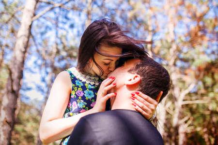 flirting women: Young couple kissing outdoor in summer sun light. Kiss love date color evening teen.
