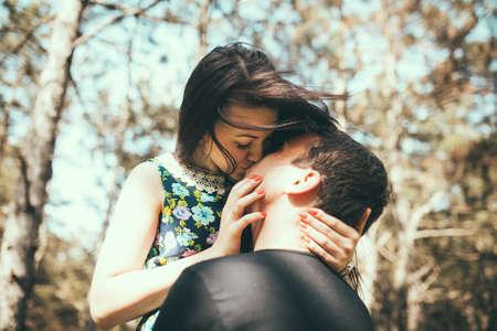 Het jonge paar kussen buiten in de zomer zonlicht. Kus liefde datum kleur avond tiener Stockfoto