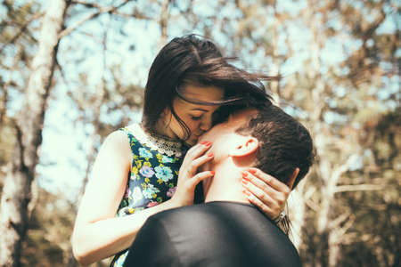 beso: Joven pareja besándose al aire libre en la luz del sol de verano. Beso fecha del amor de color la noche adolescente