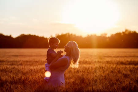 baby love: Mom and son having fun by the lake, field outdoors enjoying nature. Silhouettes on sunny sky. Warm filter and film effect