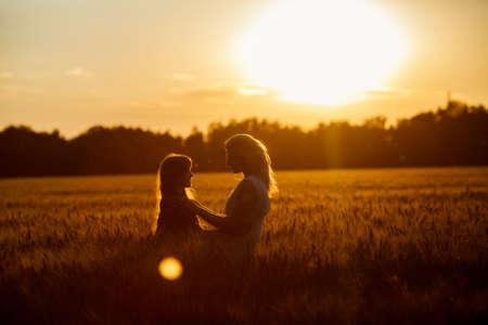 iluminado a contraluz: Hermosa joven madre feliz y su hija. La familia feliz saltando juntos en un círculo que se divierten y expresar emociones de alegría, la libertad, el éxito. Siluetas en el cielo soleado