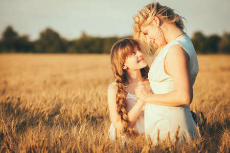 Young happy beautiful mother and her daughter. Happy family. Expressing emotions of joy, freedom, success. Silhouettes on sunny sky Banco de Imagens