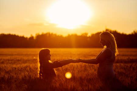 Hermosa joven madre feliz y su hija. La familia feliz saltando juntos en un círculo que se divierten y expresar emociones de alegría, la libertad, el éxito. Siluetas en el cielo soleado