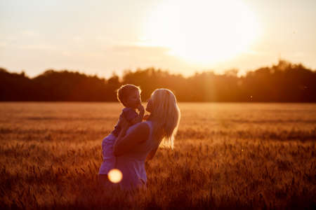 Mom and son having fun by the lake, field outdoors enjoying nature. Silhouettes on sunny sky. Warm filter and film effect