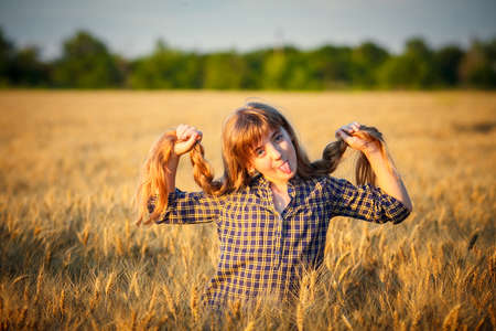 Beauty Girl Outdoors enjoying nature, raising hands. Beautiful Teenage Model girl with long healthy blowing hair running on the Spring Field, Sun Light Glow Sun. Free Happy Woman. Toned in warm colors