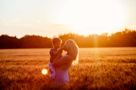 happy people: Mom and son having fun by the lake, field outdoors enjoying nature. Silhouettes on sunny sky. Warm filter and film effect
