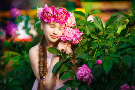 Portrait of little girl outdoors with peony
