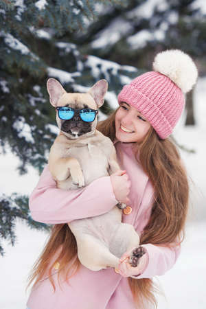 girl with a bulldog in the winter