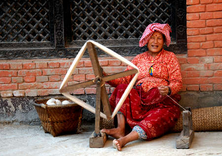demanded: A woman smiles while spinning wool thread at Khokana in Lalitpur on Thursday. Sheep wool is highly demanded during the winter season to knit different kinds of clothing to stay warm.