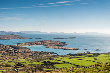 Green meadows on Irish coast  overlooking the Atlantic Ocean in County Kerry, Dingle, Ireland. Famous Ring of Kerry and Wild Atlantic Way. Stock Photo