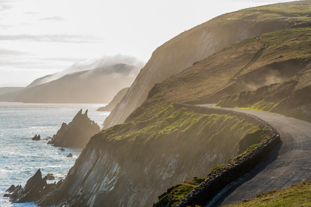 dunquin: Narrow Irish costal road in spring evening, just above the steep and dangerous cliffs. Stock Photo
